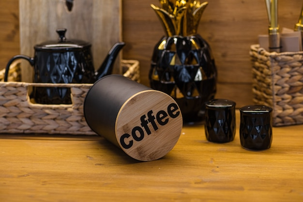 Primo piano del contenitore del caffè con la parola caffè sul coperchio sul bancone della cucina o sul tavolo con altre attrezzature da cucina come sale e pepe, teiera, cesto e tagliere di legno.