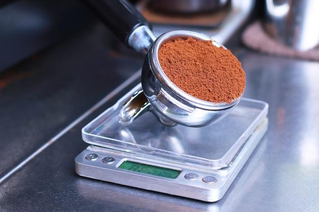Primo piano, il porta caffè si trova sulla bilancia da cucina, i chicchi di caffè macinato nel filtro