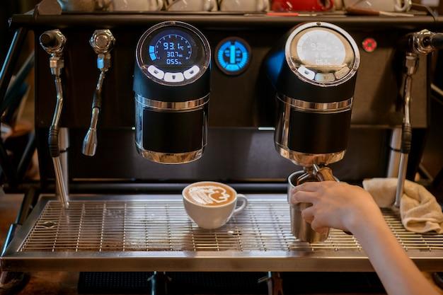 Chiuda in su della macchina per il caffè sta preparando il caffè nella caffetteria