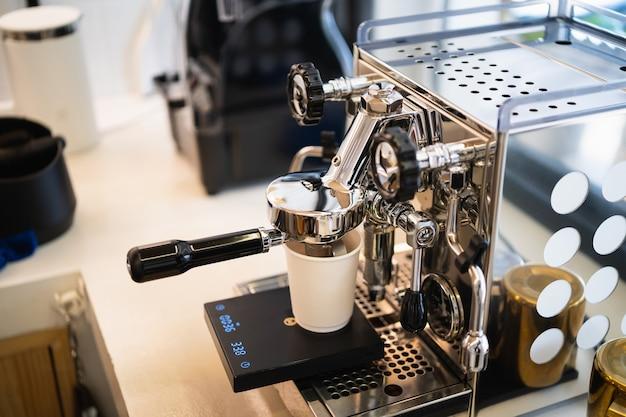 Chiuda sulla macchina del caffè che fa caffè fresco caldo