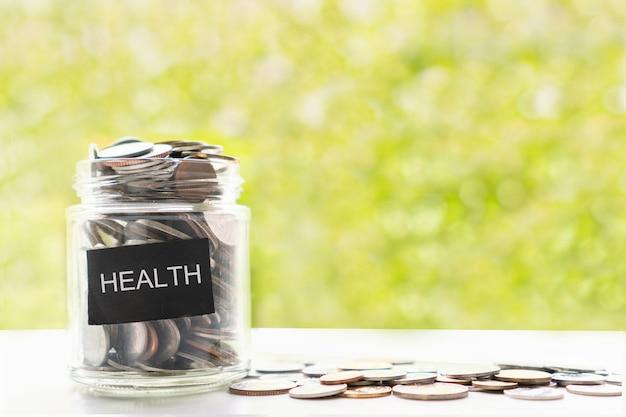Primo piano di monete in un barattolo di vetro e sul tavolo bianco su sfondo verde bokeh. raccogliere denaro per l'assistenza sanitaria medica, il risparmio e il concetto di investimento. lay piatto