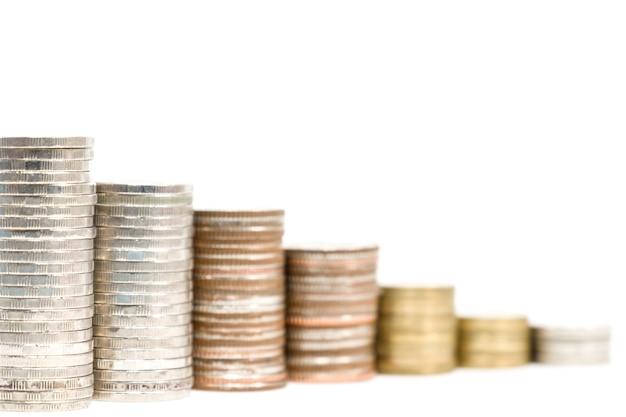 Da vicino la diminuzione della pila di monete su sfondo bianco per l'economia finanziaria e l'investitore