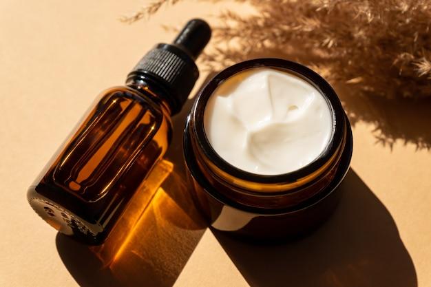 Primo piano di crema al collagene in barattolo di vetro, siero in bottiglia di vetro ambrato e canne di fiori secchi su fondo beige. set per prodotti di bellezza per la cura della pelle e del corpo.