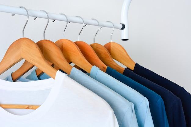 Close up collezione tonalità di magliette di colore blu tono appese su appendiabiti in legno nell'armadio
