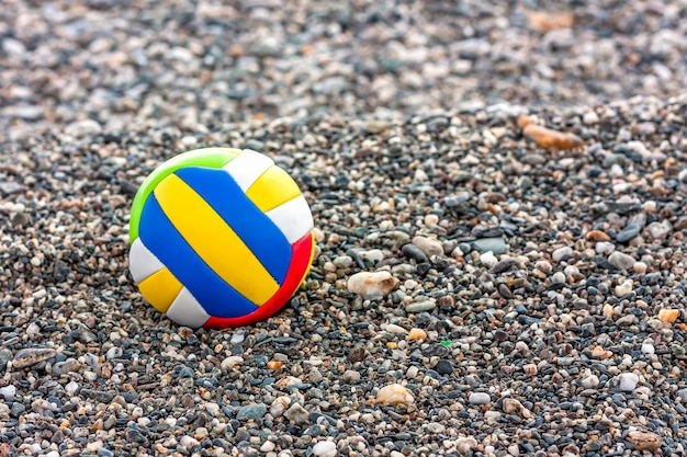 Primo piano di palla colorata per bambini su una spiaggia di ciottoli di mare. giochi da spiaggia estivi.