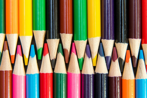 Primo piano delle matite colorate disposte nel modello di interblocco su bianco