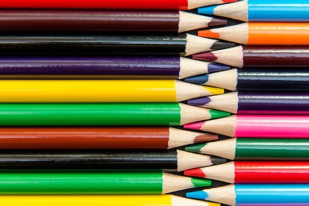 Close-up di matite colorate disposte in pattern ad incastro.
