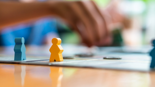 Chiuda sulle figure variopinte della parte della gente sulla tavola con l'amico che gioca, gioco da tavolo divertente ca