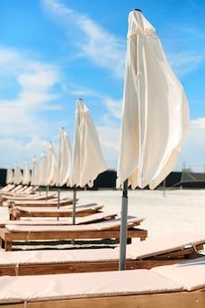 Primo piano di comodi lettini con ombrelloni chiusi disposti sulla spiaggia sabbiosa. bel resort per il relax. vacanza durante il periodo estivo.