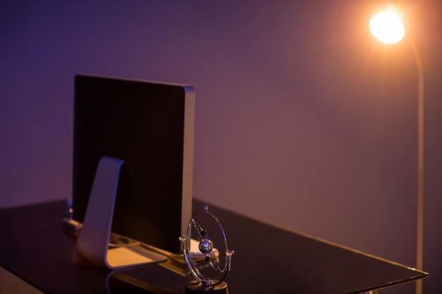 Monitor del computer del primo piano e lampada illuminata