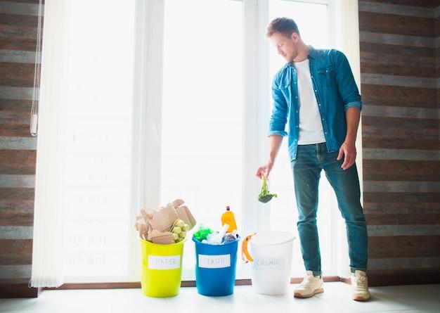 Concetto di primo piano. ordina i rifiuti a casa. esistono tre secchi per diversi tipi di immondizia. guy ordina i rifiuti in cucina