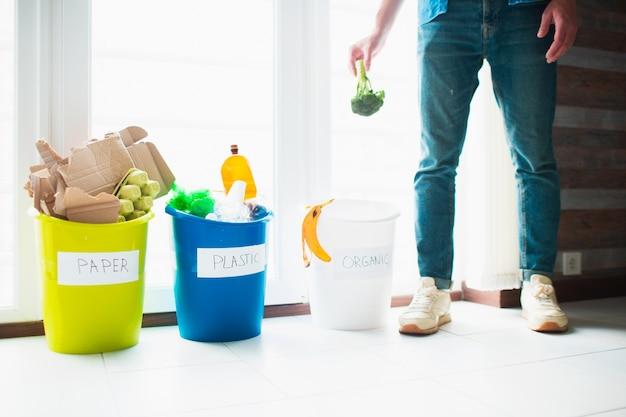 Concetto di primo piano. ordina la spazzatura a casa. ci sono tre secchi per diversi tipi di spazzatura. guy ordina i rifiuti in cucina.