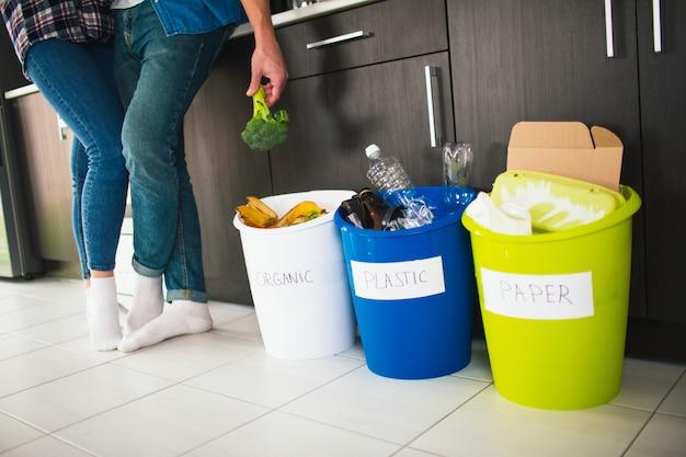 Concetto di primo piano. ordina i rifiuti a casa. esistono tre secchi per diversi tipi di immondizia. la giovane famiglia ordina i rifiuti in cucina