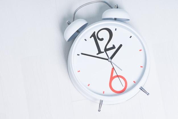 Primo piano concettuale mentre la sveglia, enfatizzando la sveglia alle 5, isolata su sfondo bianco
