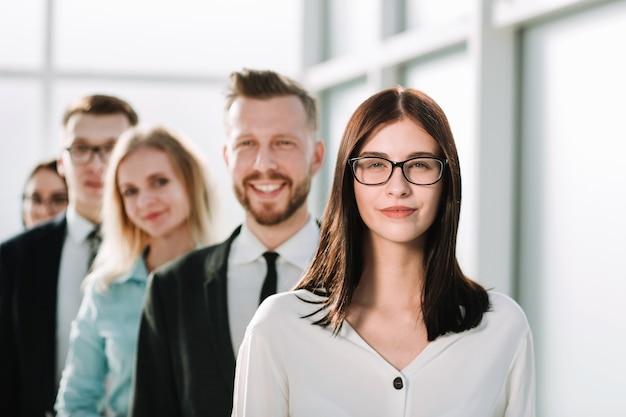 Avvicinamento. donna d'affari fiduciosa in piedi davanti al suo team di affari. il concetto di lavoro di squadra