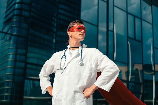 Primo piano giovane medico fiducioso in un mantello da supereroe