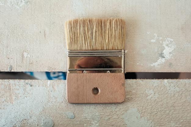 Primo piano della spazzola da costruzione del tavolo in legno.