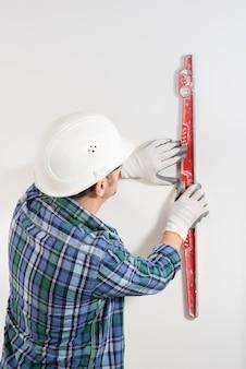 Primo piano di un operaio edile in un casco di sicurezza che ispeziona un muro bianco liscio in un cantiere edile
