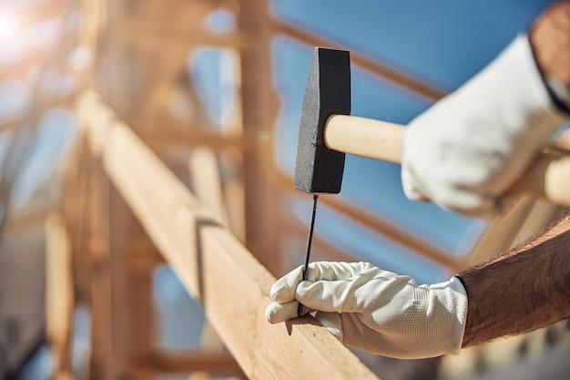 Primo piano del costruttore che martella il chiodo