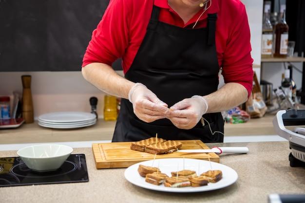 Primo piano dell'uomo cuoco in guanti di gomma preparare spuntini panini alla griglia. messa a fuoco morbida, lo sfondo è la cucina sfocata