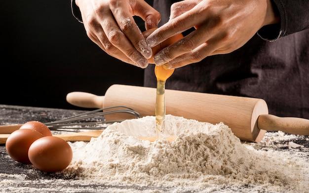 Uovo di versamento del cuoco del primo piano su farina