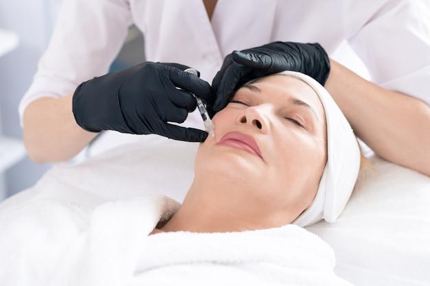 Primo piano del cosmetologo in guanti chirurgici che inietta il riempitivo al cliente mentre rimuove le rughe intorno alla bocca