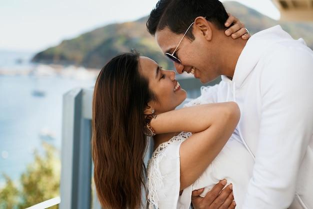 Chiuda sulle coppie che abbracciano sul balcone con vista sull'oceano, il ragazzo indiano del brunette abbraccia la ragazza asiatica in vestiti bianchi.