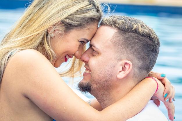 Primo piano di coppia vicino alla piscina, con la faccia incollata e sorridente.