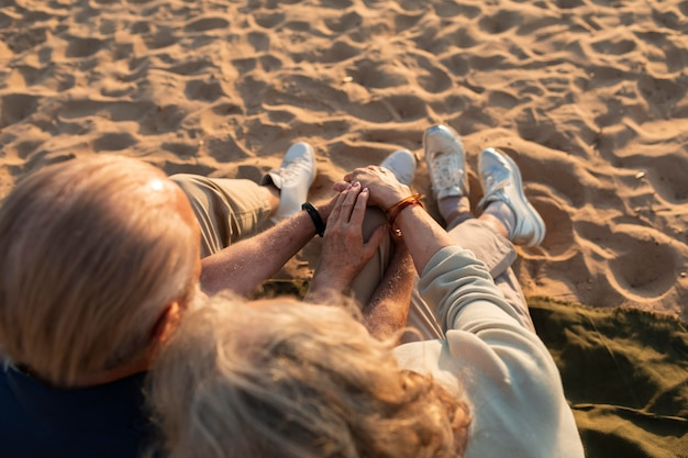 Primo piano coppia seduta sulla spiaggia