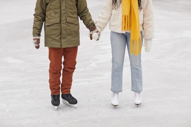 Primo piano di coppia in abiti caldi in piedi sulla pista di pattinaggio e tenendosi per mano