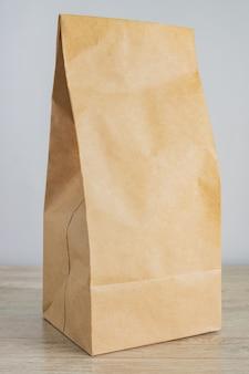 Chiuda in su del sacco di carta in bianco del mestiere per la consegna dell'alimento. concetto di acquisto e consegna
