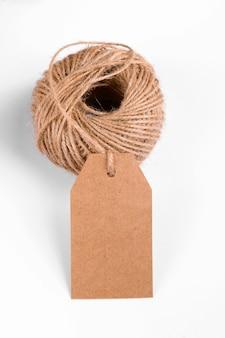 Close-up di carta artigianale regalo tag con matassa di corda su sfondo bianco.