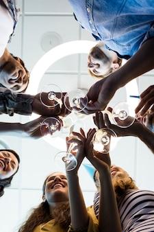 Primo piano della squadra creativa di affari che ha un brindisi sul compleanno del college in ufficio