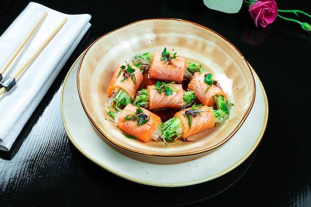 Chiuda in su sul rotolo di sushi fatto creativo con i salmoni, il microgreen, il cetriolo. sashimi di color salmone delizioso in ciotola gialla con la salsa di soia su oscurità. cucina giapponese. frutti di mare, pesce crudo.