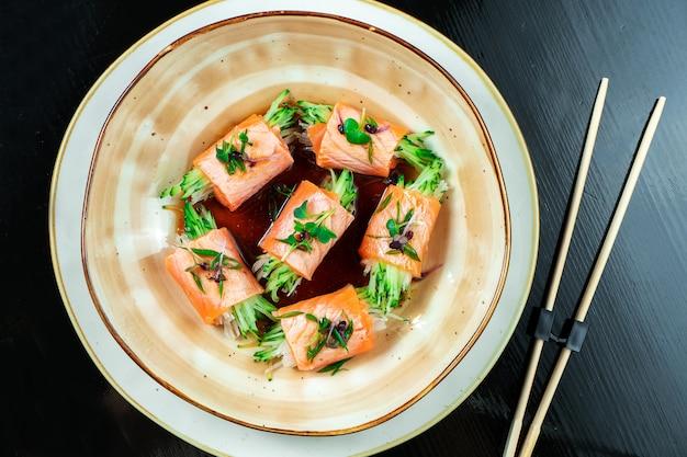 Chiuda in su sul rotolo di sushi fatto creativo con i salmoni, il microgreen, il cetriolo.