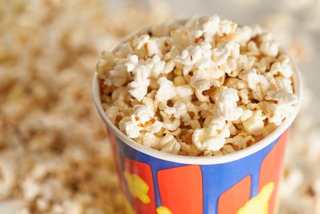 Primo piano di croccanti popcorn fritti in scatola a strisce. concetto di cibo gustoso.