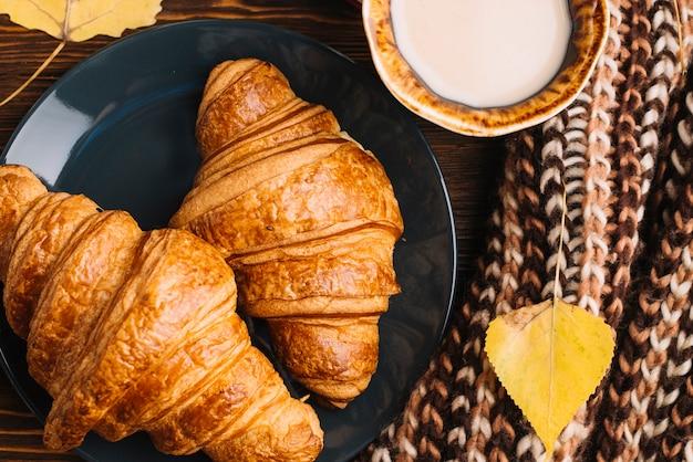 Croissant e bevanda del primo piano vicino a foglia e sciarpa