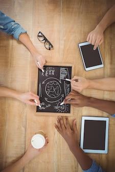 Primo piano delle mani potate che scrivono i termini di affari sull'ardesia con la compressa digitale commovente della persona alla linguetta