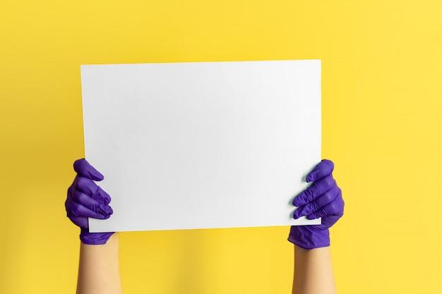 Chiuda sulla tenuta potata nel bordo bianco bianco del segno vuoto in bianco delle mani grande per il contenuto promozionale, indicando il dito sul posto per testo isolato. copia spazio pubblicitario