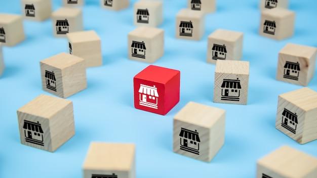 Chiuda sui blocchi di legno del giocattolo del cubo con l'icona del negozio di affari di franchising