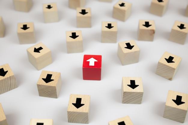 Blog di giocattoli di legno del cubo del primo piano con le icone della testa della freccia che indicano le direzioni opposte per il cambiamento di affari.
