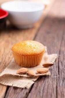 Chiudere una tazza di torta di mandorle contro il tessuto del sacco sul tavolo di legno