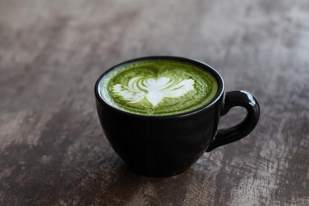 Primo piano di una tazza di tè verde matcha bevanda calda di arte tarda sul fondo della tavola in legno