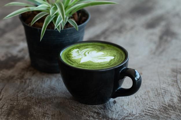 Primo piano di una tazza di tè verde matcha bevanda calda di arte tardiva sul tavolo di legno