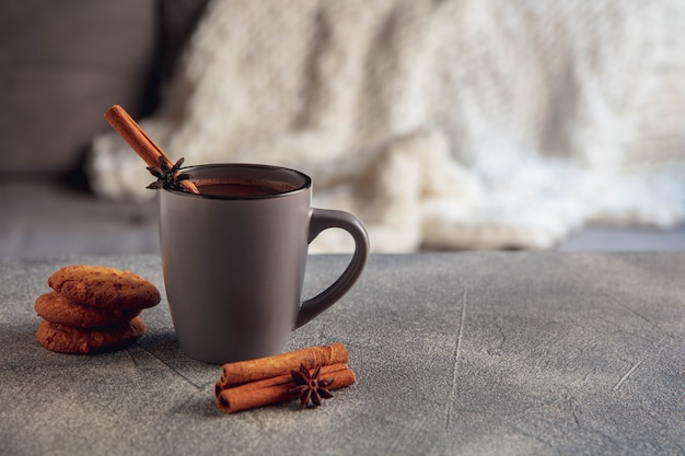 Avvicinamento. tazza di tè o caffè con cannella e biscotti isolati su sfondo grigio e bianco. il concetto di atmosfera domestica e comfort, vacanze, appuntamento romantico, inverno, natale o capodanno.