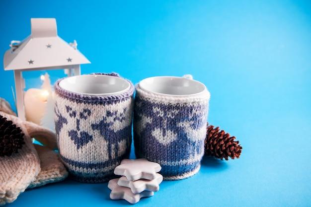 Close up tazze di bevanda calda con coperture lavorate a maglia