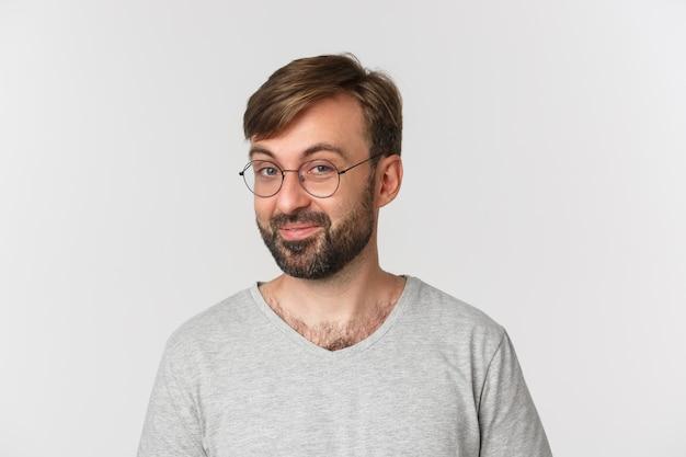 Primo piano dell'uomo barbuto curioso in maglietta grigia e occhiali