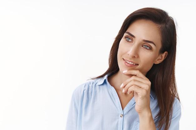 Close-up curiosa donna d'affari soddisfatta ascolta le idee dei dipendenti durante la riunione, inclina la testa tocca il mento incuriosito, sorride guardando copia spazio lato sinistro sorriso soddisfatto, prendendo decisione, muro bianco