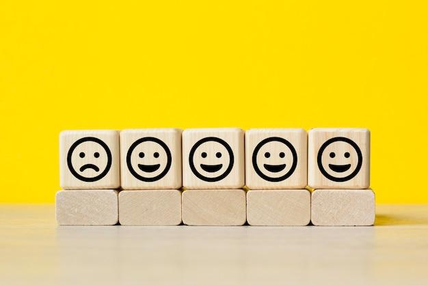 Close up custome scegliere l'icona del viso sul cubo di legno, valutazione del servizio, concetto di soddisfazione.