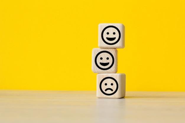 Close up custome scegliere faccina sorridente e sfocata icona faccia triste sul cubo di legno, valutazione del servizio, concetto di soddisfazione.